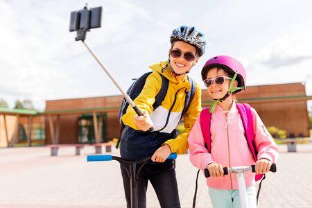 happy school kids with scooters taking selfie Stockfoto
