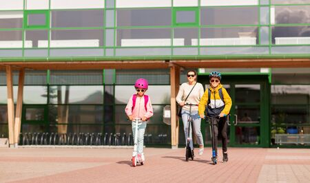 happy school children with mother riding scooters