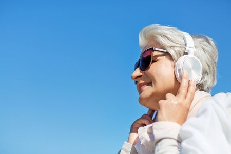 old woman in headphones listens to music outdoors