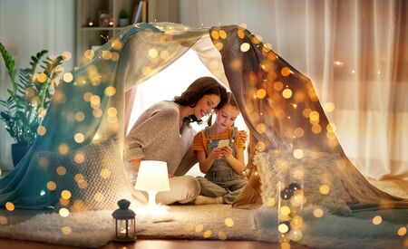 happy family with smartphone in kids tent at home