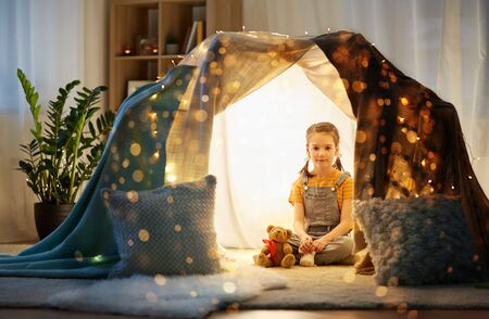 little girl with toys in kids tent at home