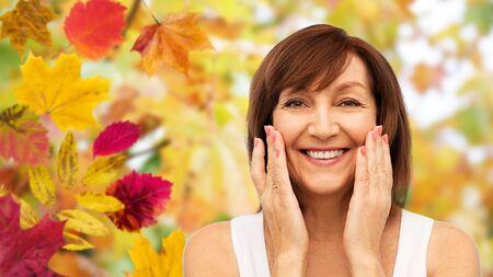 portrait of smiling senior woman touching her face 版權商用圖片