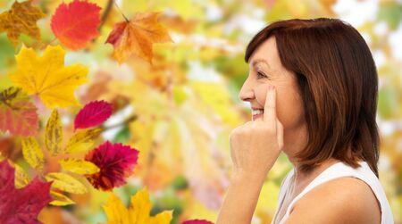 profile of senior woman pointing to eye wrinkles Banco de Imagens