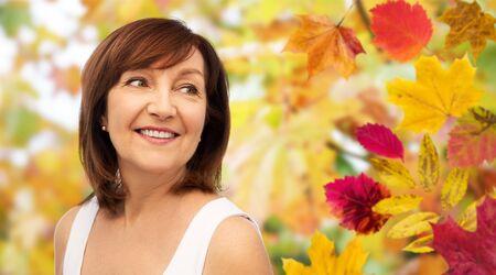 portret szczęśliwej starszej kobiety nad jesiennymi liśćmi
