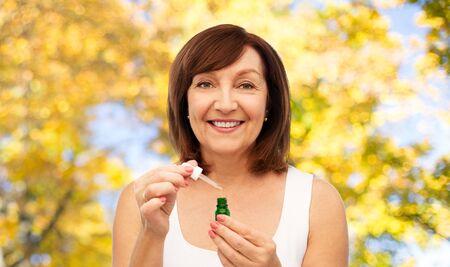 smiling senior woman with bottle of serum