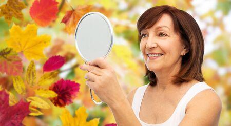 portrait of smiling senior woman with mirror 版權商用圖片