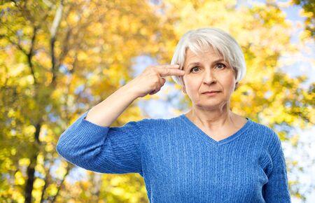 old woman making finger gun gesture in autumn park
