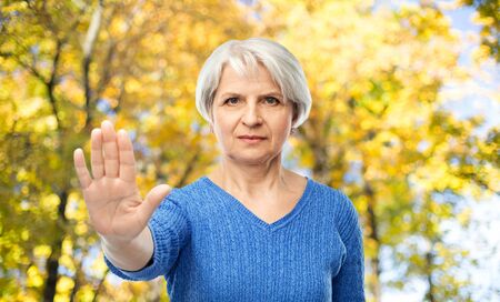 senior woman making stop gesture in autumn park