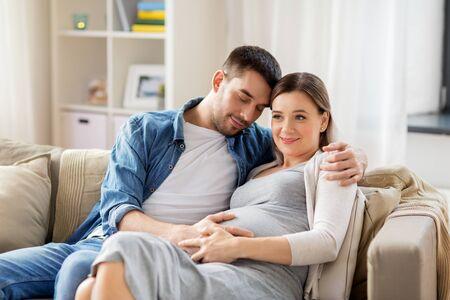 man hugging pregnant woman at home