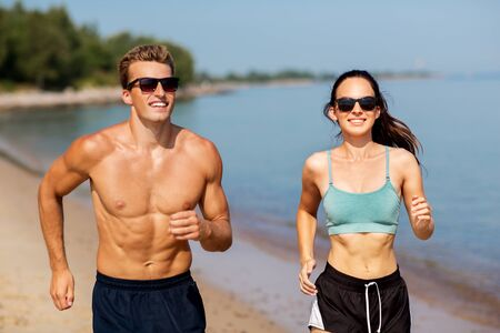 couple in sports clothes running along on beach Imagens