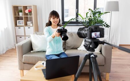asian female blogger with camera recording video Imagens