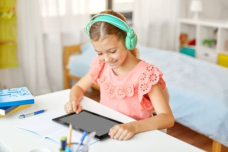 girl in headphones with tablet computer at home Imagens