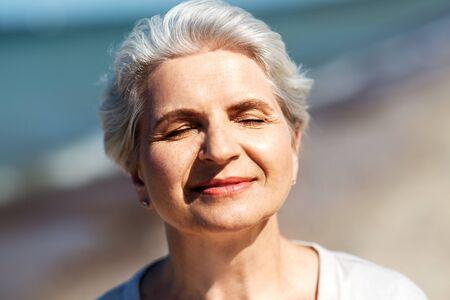 portrait of senior woman enjoying sun on beach