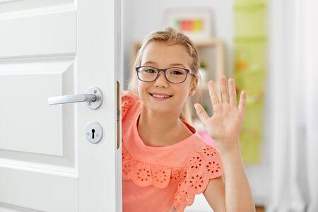 heureuse belle fille souriante derrière la porte à la maison Banque d'images