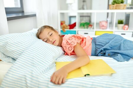 little girl with book sleeping in her room at home