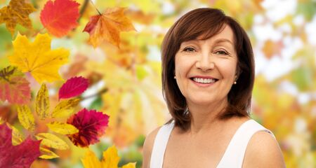 beauty and old people concept - portrait of smiling senior woman over autumn leaves and nature background