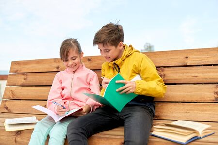 school children with notebooks sitting on bench Stock Photo