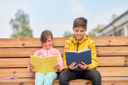 school children reading books sitting on bench