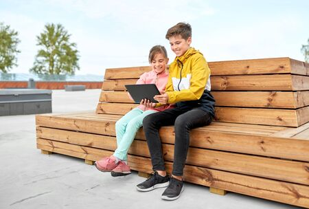 children with tablet computer sitting on bench