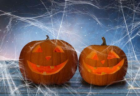 two pumpkins or jack o lanterns and spiderweb Stockfoto