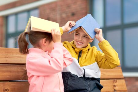 school children with books having fun outdoors