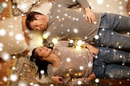 happy couple lying on floor at home