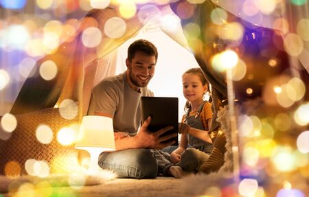 family with tablet pc in kids tent at home Stock fotó