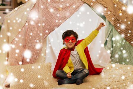 happy boy in super hero stuff in kids tent at home