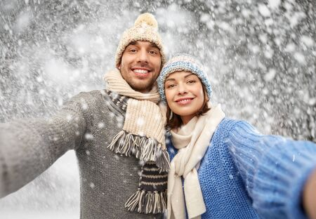 happy couple in winter clothes taking selfie