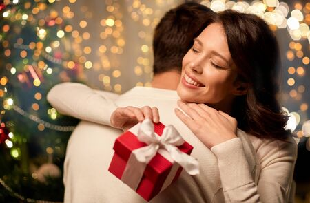 happy couple with christmas gift hugging at home 스톡 콘텐츠