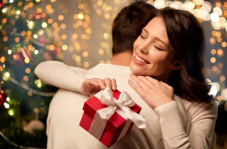 gelukkig paar met kerstcadeau knuffelen thuis Stockfoto