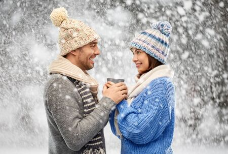 happy couple in winter clothes holding one cup