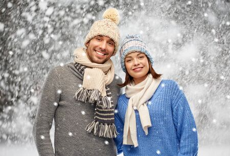 happy couple in winter clothes over snow