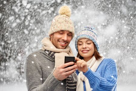 happy couple in winter clothes with smartphone Stockfoto