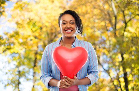 donna afroamericana con palloncino a forma di cuore Archivio Fotografico