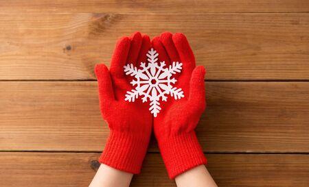 hands in red woollen gloves holding big snowflake