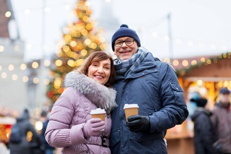 senior couple with coffee at christmas market