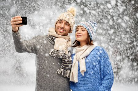 couple in winter hats taking selfie by smartphone