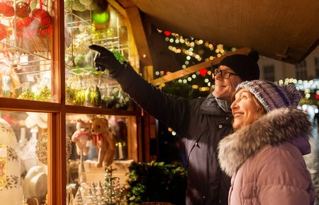 shopping, winter holidays and people concept - happy senior couple at christmas market souvenir shop window on town hall square in tallinn, estonia