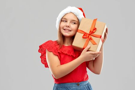 christmas, childhood and holidays concept - smiling girl posing in snata helper hat with gift box over grey background Stock Photo