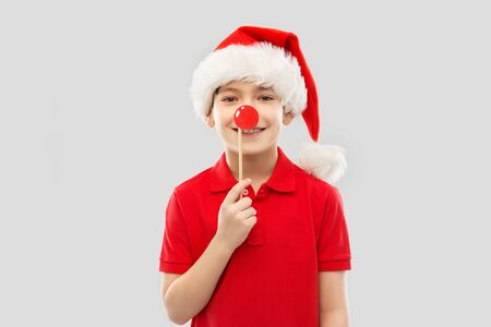 christmas, holidays and childhood concept - smiling little boy in red polo t-shirt and santa helper hat over grey background