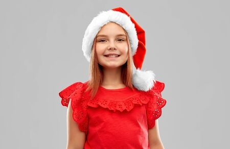 christmas, childhood and holidays concept - smiling girl posing in snata helper hat over grey background