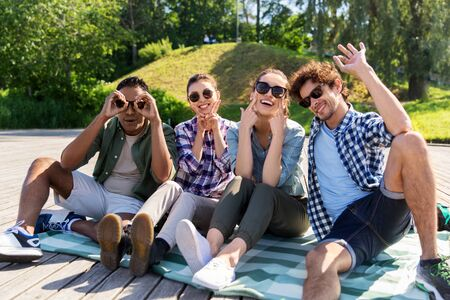 leisure and people concept - friends hanging out and making faces outdoors at summer park