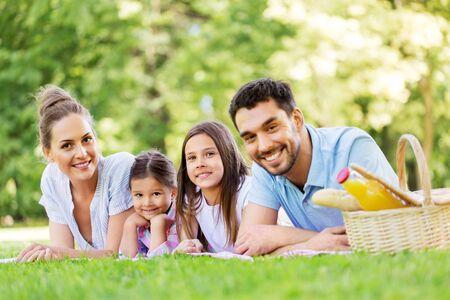 家族、レジャー、人々のコンセプト - 幸せな母親、父と2人の娘が夏の公園でピクニック毛布の上に横たわっている 写真素材