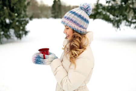 happy young woman with tea cup outdoors in winter Stock Photo