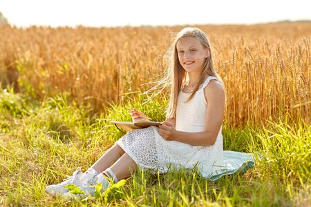 smiling girl writing to diary on cereal field