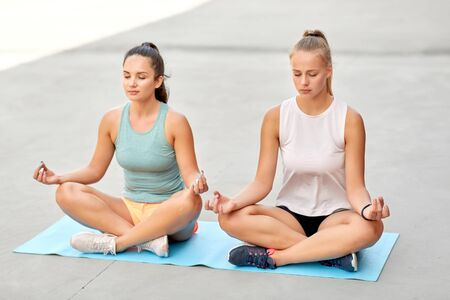 women doing yoga and meditating in lotus pose