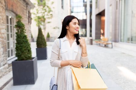 asian woman with shopping bags walking in city