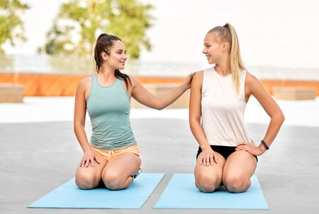 happy women sitting on exercise mats outdoors