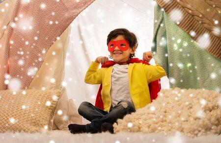 happy boy in super hero cape in kids tent at home
